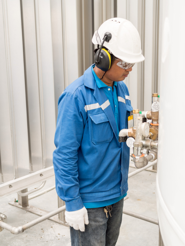 Engineer working with safety ear muffs helmet and gloves for ind